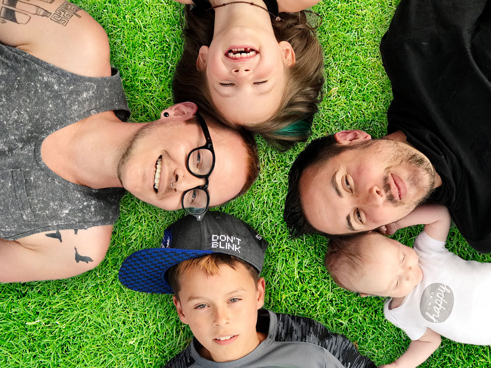 Trystan Reese and his family lying in the grass